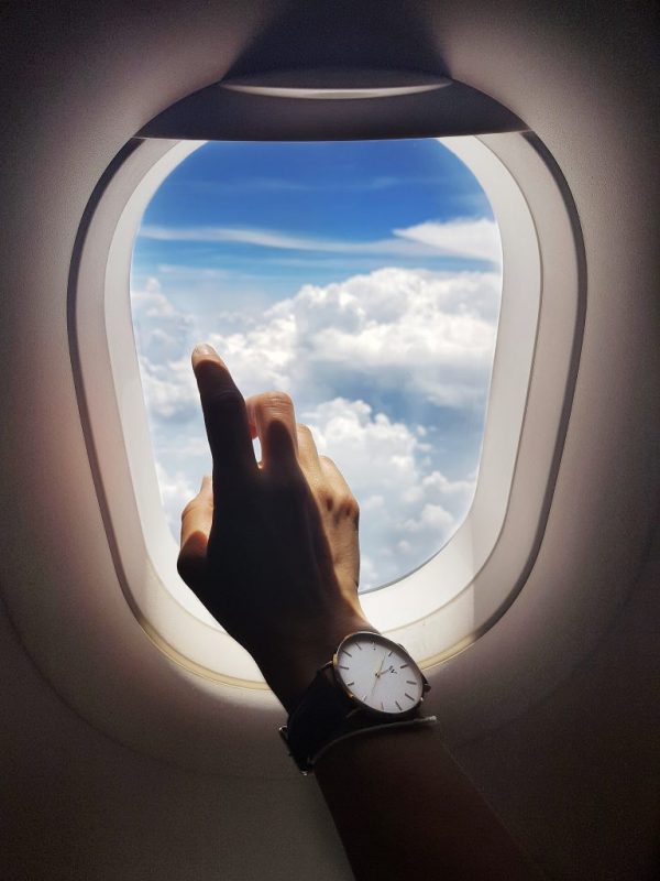 hand infront of window seat plane